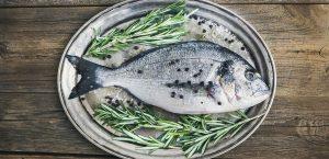 Fresh sea fish (sea bream) on a metal dish with rosemary and spi Anna Ivanova