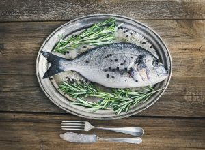 Fresh sea fish (sea bream) on a metal dish with rosemary and spi Foxy's Forest Manufacture-iStock
