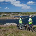 Cyclists overlooking Little Porth, Isles of Scilly