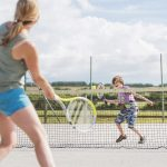 Woman and boy playing tennis