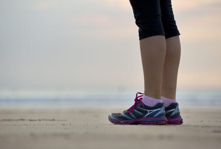 Woman standing in running gear on a sandy beach