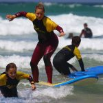 Teenage girl enjoying a surf lesson with The Headland Hotel's surf school