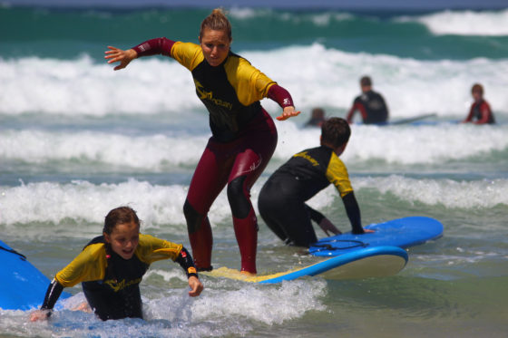 Teenage girl enjoying a surf lesson with The Headland Hotel's surf school The Headland Hotel