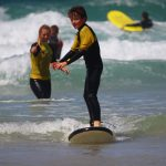 Young teenage boy enjoying a surf lesson with The Headland Hotel's surf school