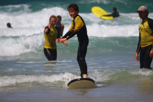 Young teenage boy enjoying a surf lesson with The Headland Hotel's surf school The Headland Hotel