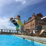Young children jumping into The Headland Hotel's outdoor swimming pool