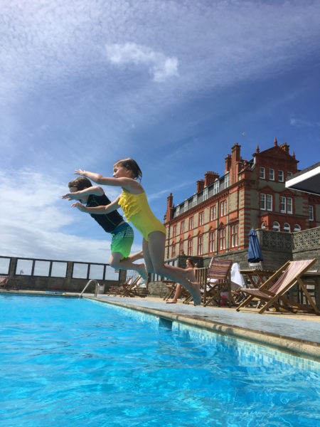 Young children jumping into The Headland Hotel's outdoor swimming pool The Headland Hotel