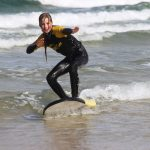 Young teenage girl enjoying a surf lesson with The Headland Hotel's surf school