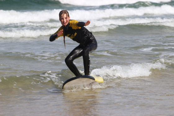 Young teenage girl enjoying a surf lesson with The Headland Hotel's surf school The Headland Hotel