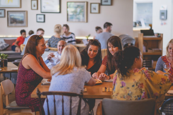 Friends and family sharing a pizza at Una Kitchen