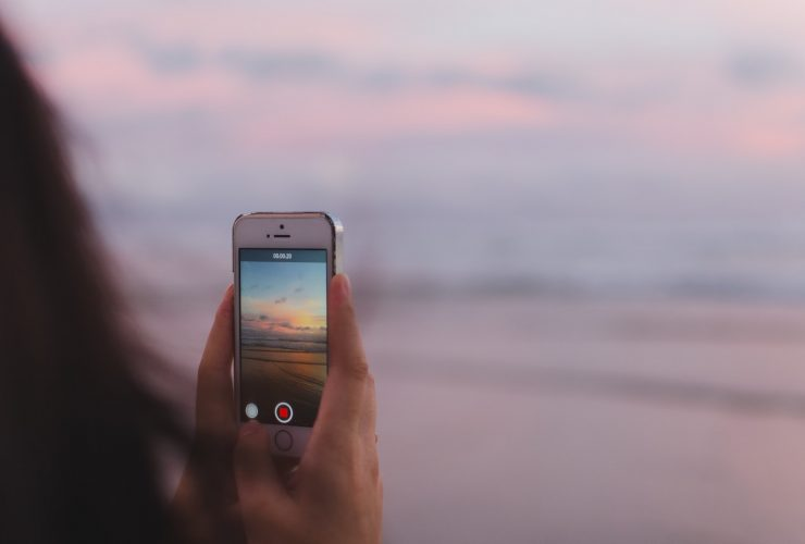 Shooting a video on a phone at the beach