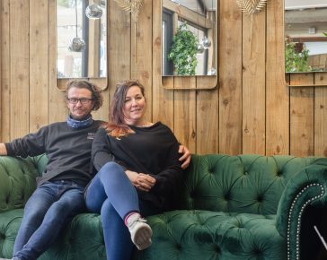 Couple sat on a green velvet sofa in a garden centre
