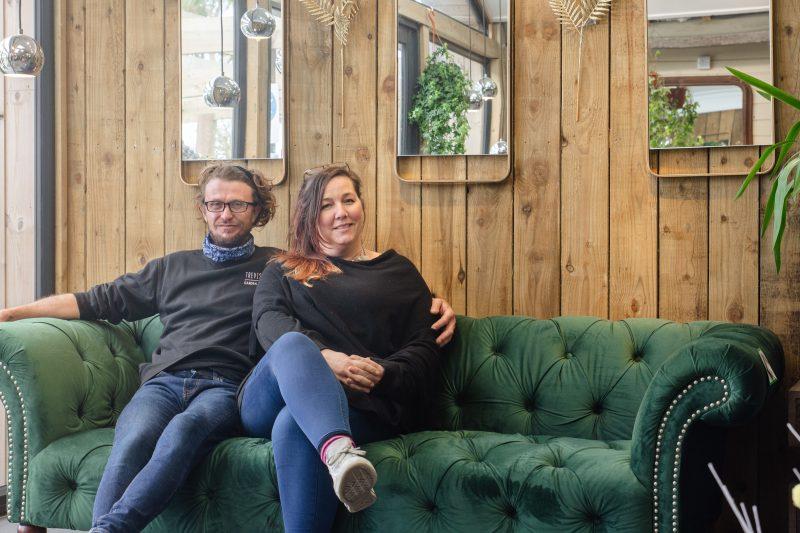 Couple sat on a green velvet sofa in a garden centre